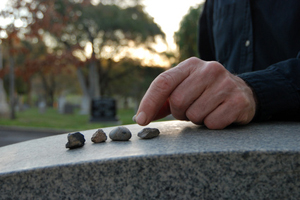 Close up of a left hand leaving a pebble on a headstone in cemetery.